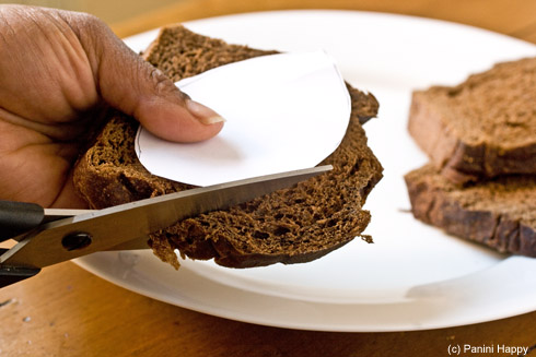 Draw a football-shaped template on a piece of paper and cut the shape out of bread with kitchen shears